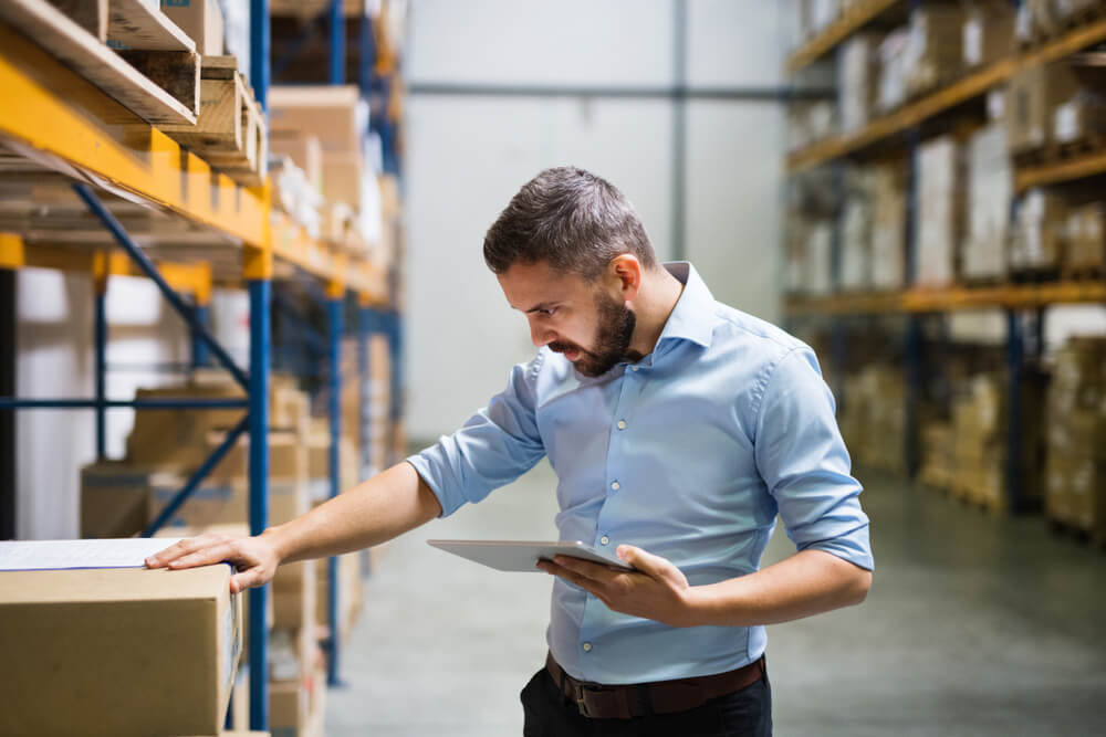 A worker checking inventory in a big warehouse facility full of inventories