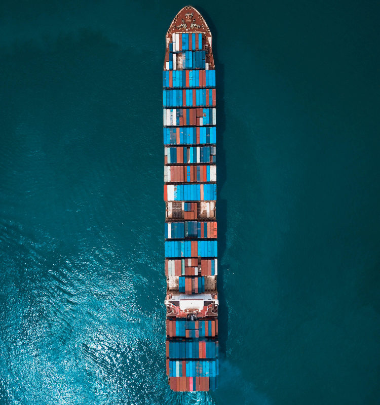 Aerial view of a cargo ship full of metal containers heading to sea