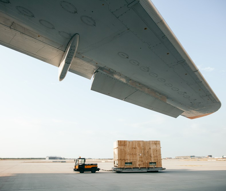Picture of a truck pulling a cargo box in an airport runway