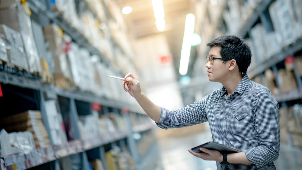Man checking inventory in a big warehouse facility
