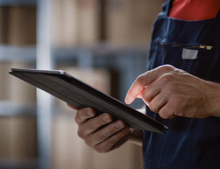 A worker checking inventory in a warehouse facility