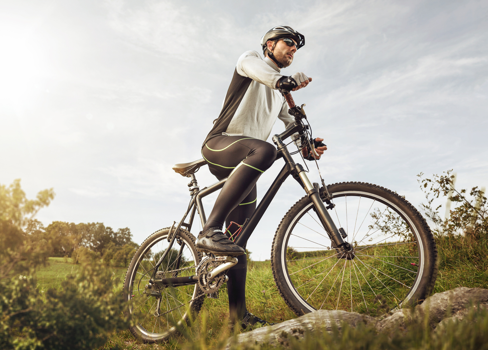 Cyclist on grassy field during mid day