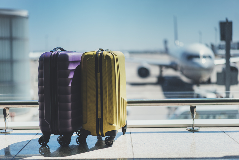 Luggage in an airport with an airplane in the background