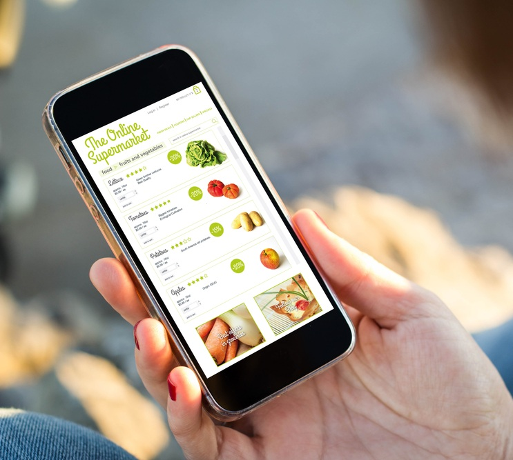 A mobile phone with online supermarket app on screen