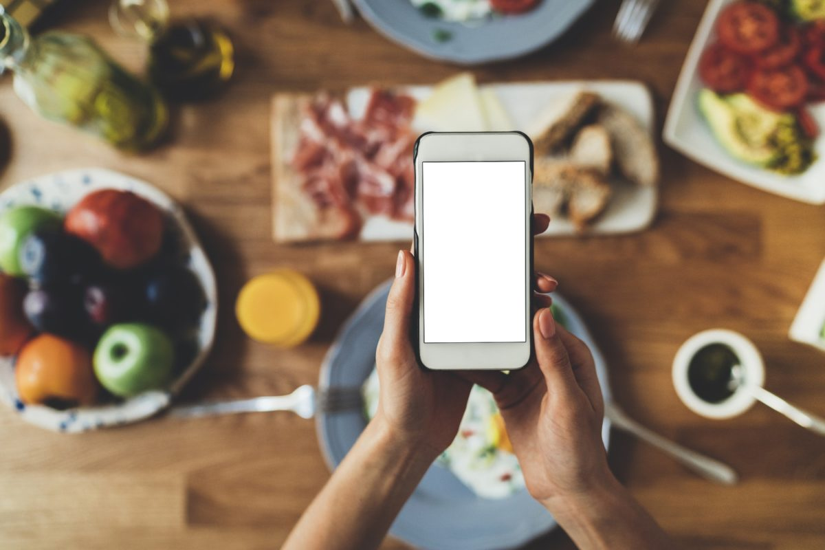A mobile phone with table full of food in the background