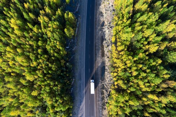 Aerial view of a delivery truck on a road through a forest