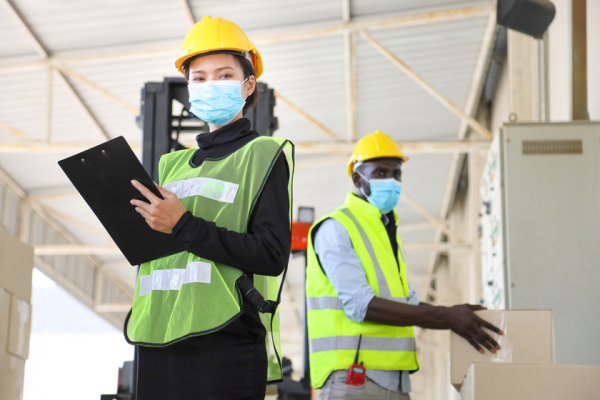 Engineers wearing facemask working on a warehouse
