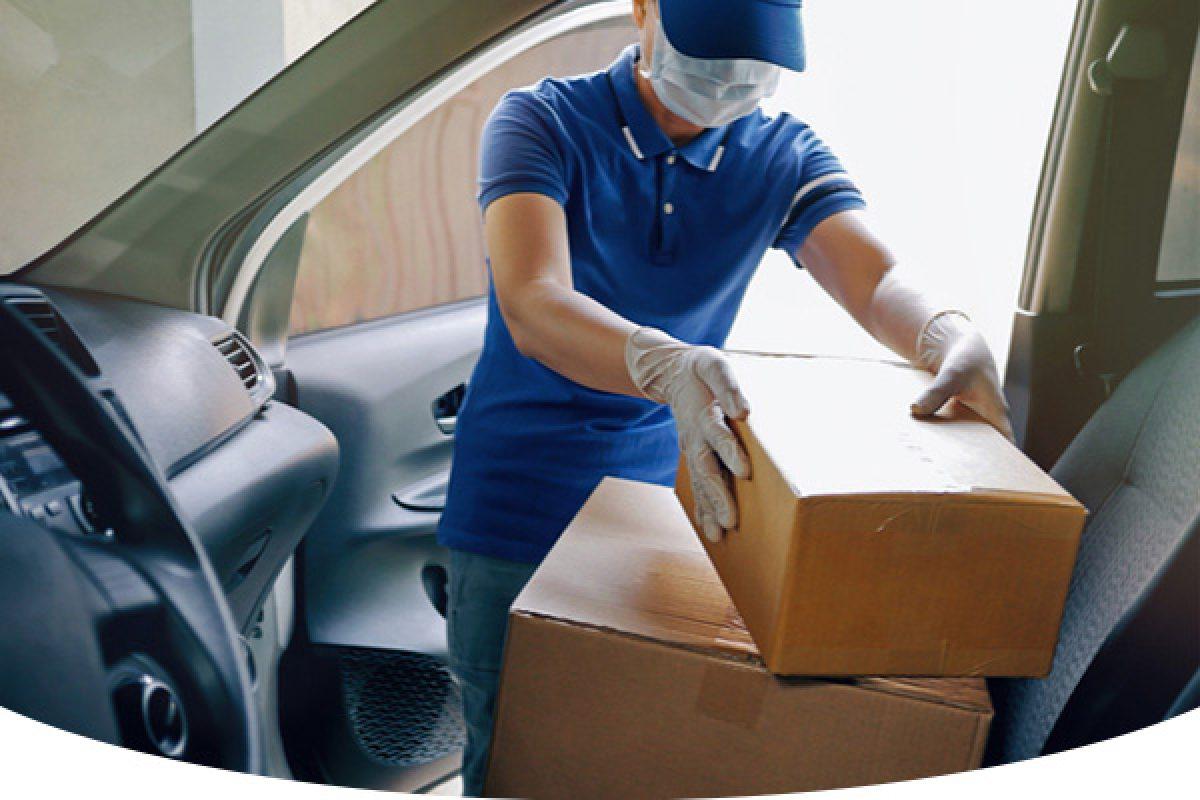 Man wearing mask taking boxes out of car