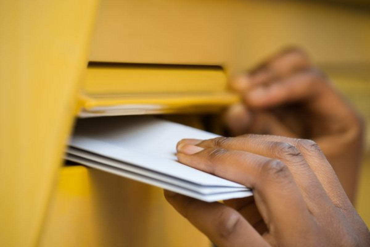 Person putting mails in a mailbox