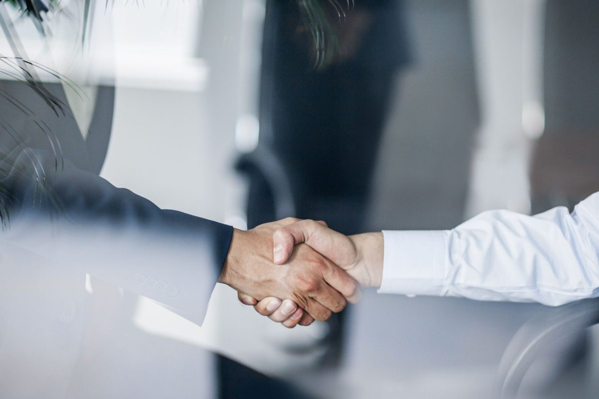 business-handshake-in-glass-reflection-in-office-675872871-31a95e1d4fd8433088e738228fd9d3dc