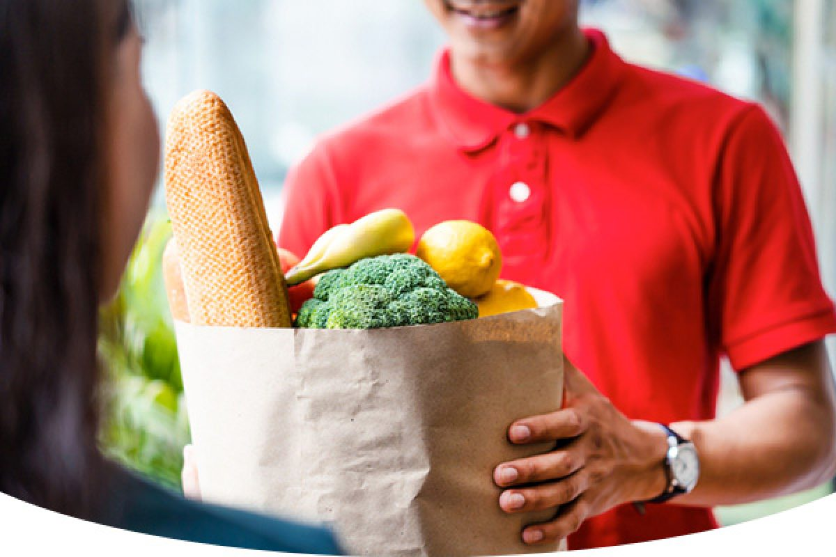 man handing over grocery bag to woman