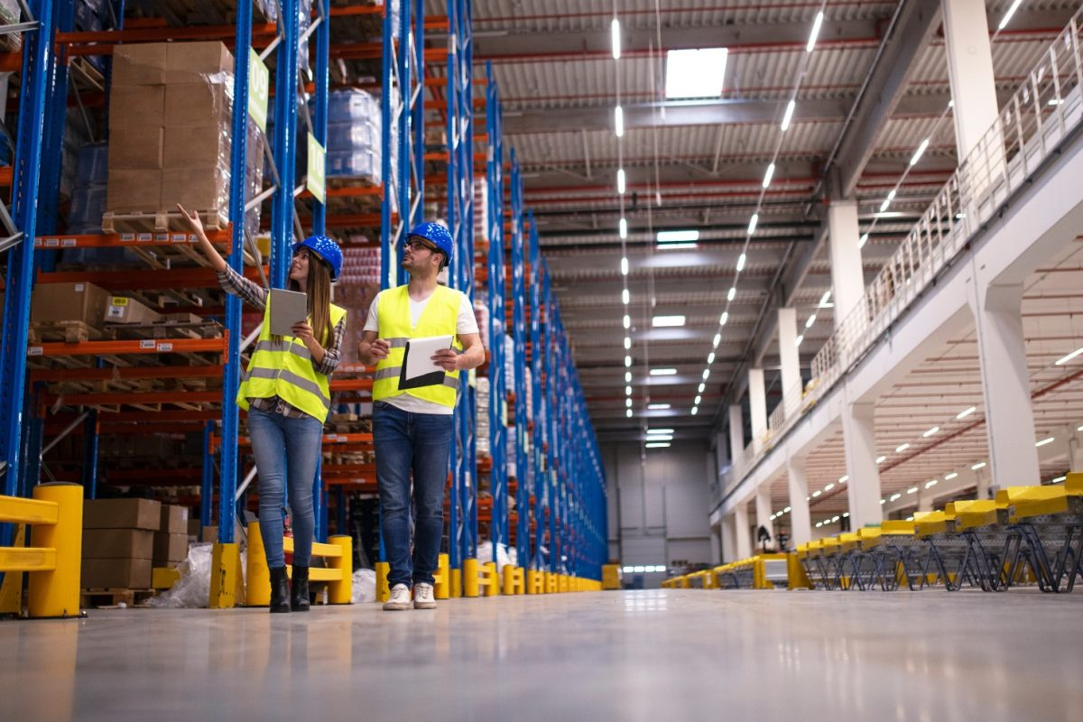 Workers in a big warehouse facility full of inventories